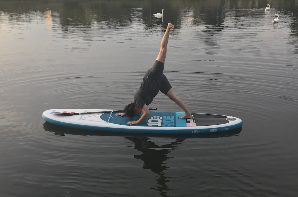 Woman doing yoga on a stand up paddleboard on the Thames