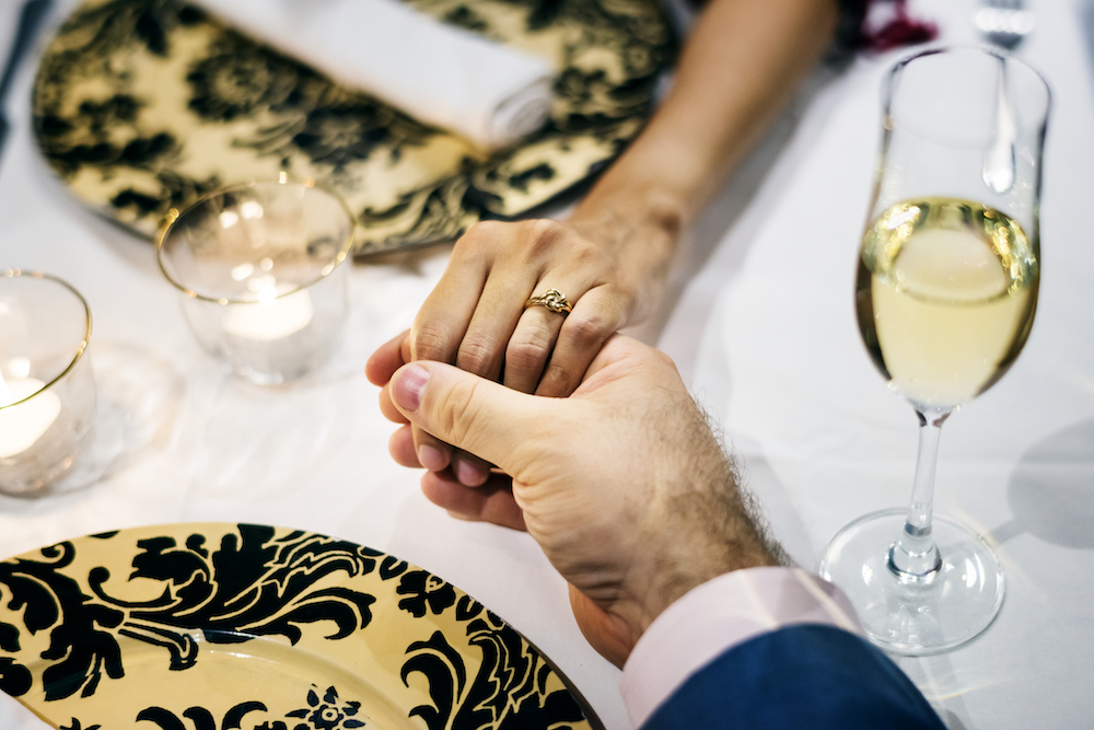 Couple hold hands at dinner with wine, wedding wine