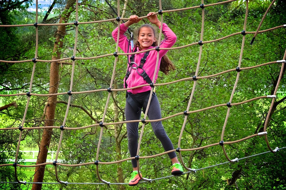 girl on rope climbing frame in trees