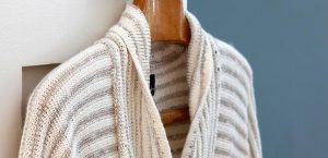 beige and cream knitted cardigan on wooden coat hanger