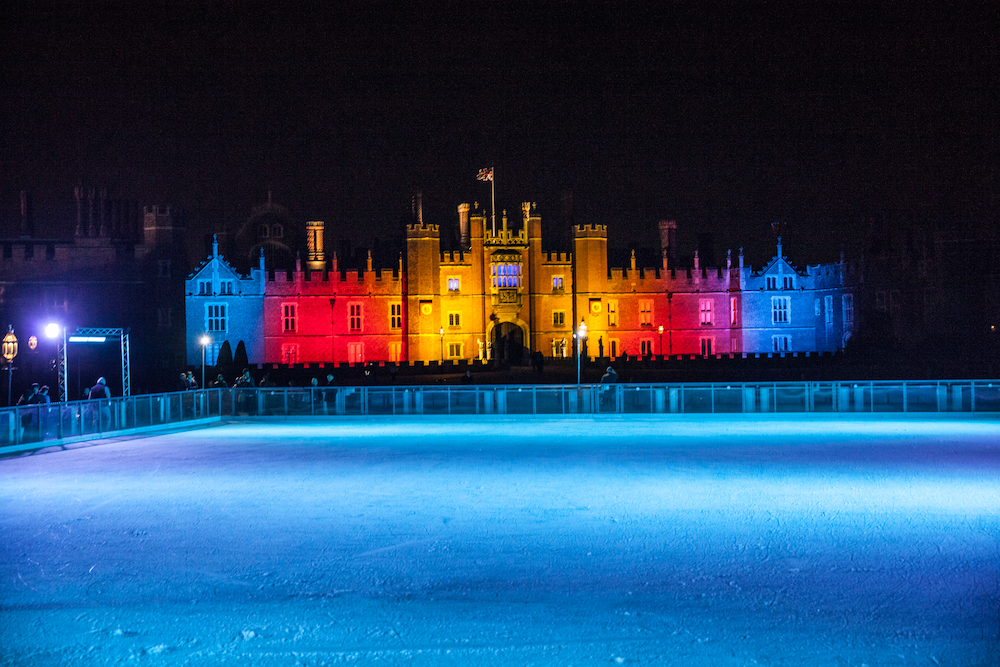 Hampton court palace illuminated with coloured lights pop up ice rink in front